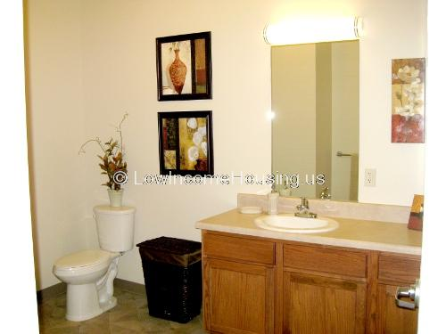 This is a photograph of a toilet room equipped with a toilet, a sink, a mirror, and storage areas for towels and sundries.