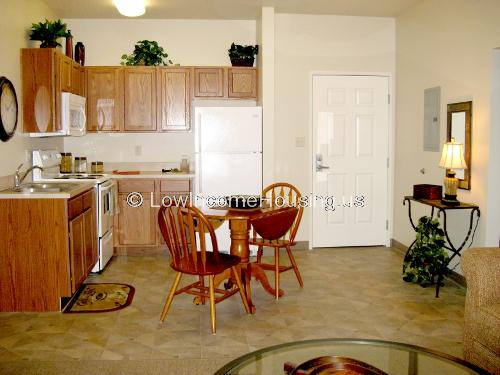 Interior of a kitchen equipped with a gas range, a twin sink, a refrigerator/freezer and several storage cabinets a small table and two chairs.