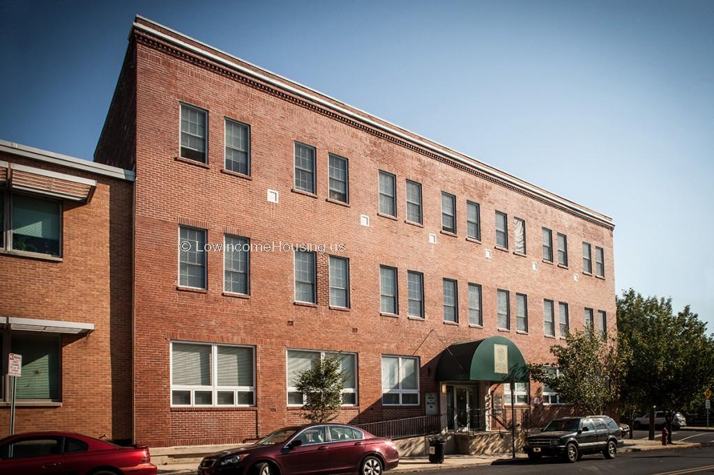 Large, red brick three story apartment building with 18 apartments per floor. Ground floor with large double sized picture windows.  Convenient curbside parking is available for residents.
