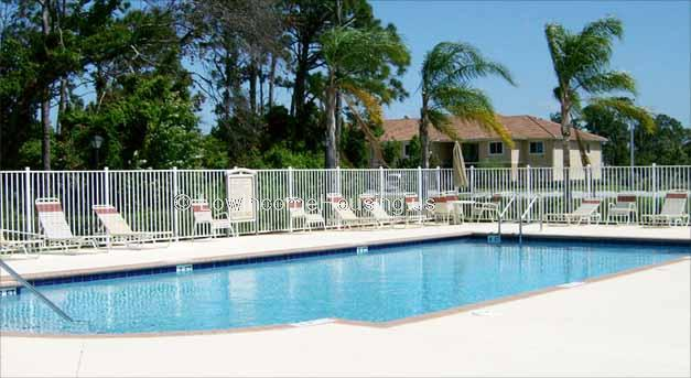Large swimming pool with ample number of lawn chairs for sun bathing.