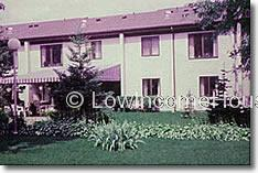 Photograph of two story row houses with installed awnings and beautifully maintained flower beds.