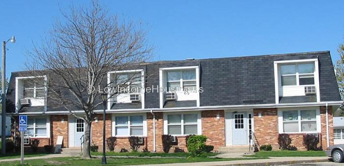 Classic red brick row house with two units.  Each unit has a large, floor to ceiling window with air conditioning unit installed.