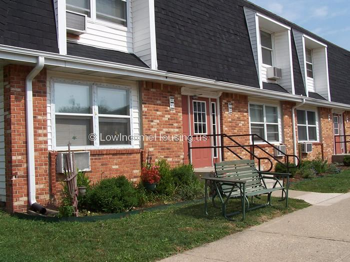 2 housing units with Red brick, large windows and air conditioners installed.