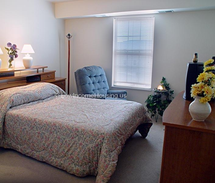 Large, comfortable king size bed, floor to ceiling window  with large arm chair, television and bureau.