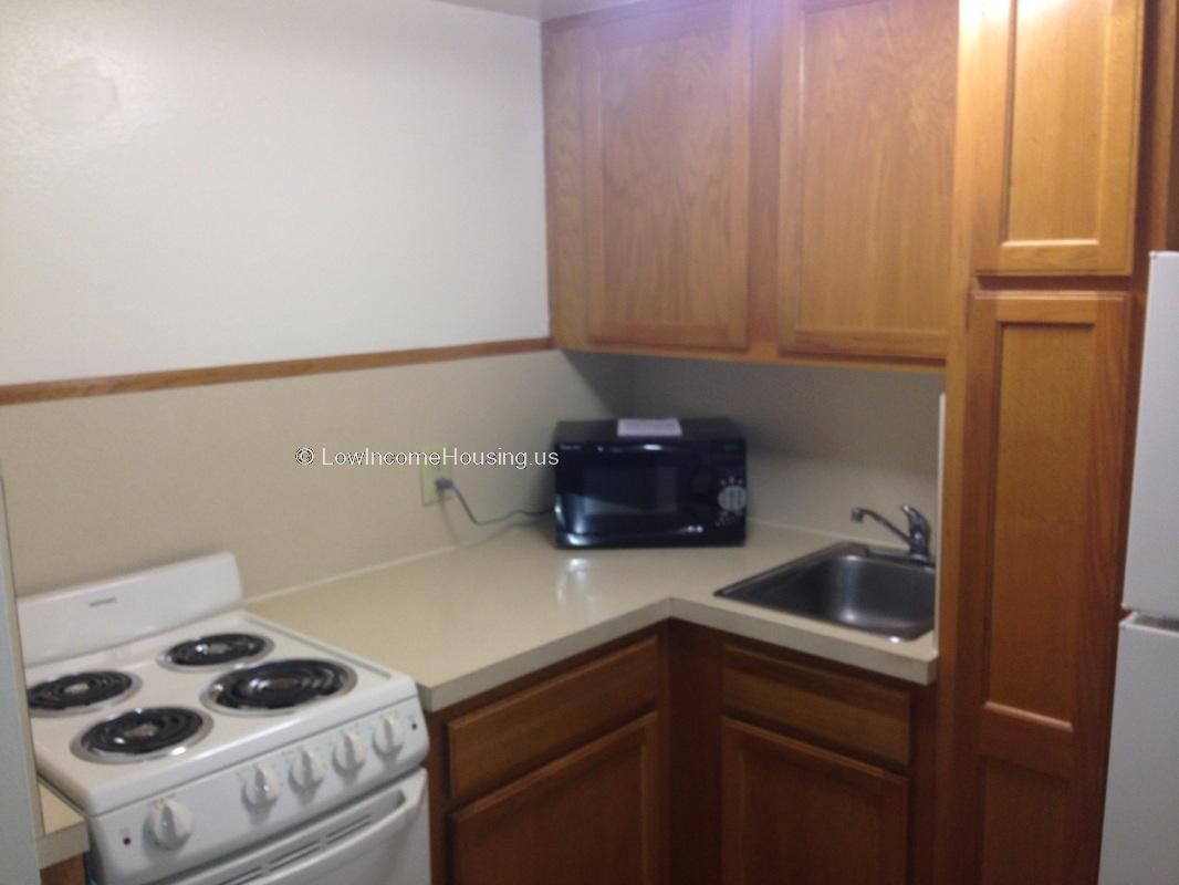 Photograph of apartment kitchen, stove with four burners, oven, ample supply of closet an drawer space.