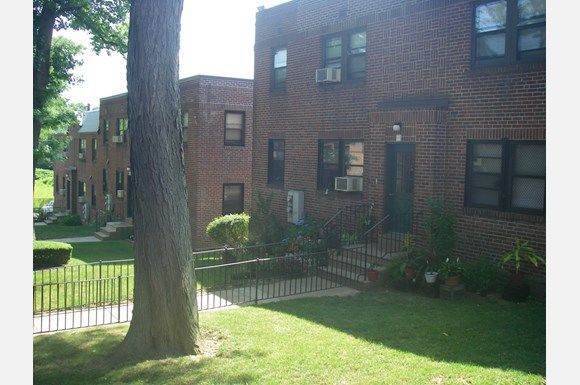 There are three large red brick buildings with window mounted air conditioners visible in all of the windows.