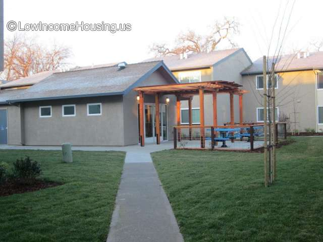 Large single unit housing block with exterior wooden cover over entrance, exterior seating with picnic table.