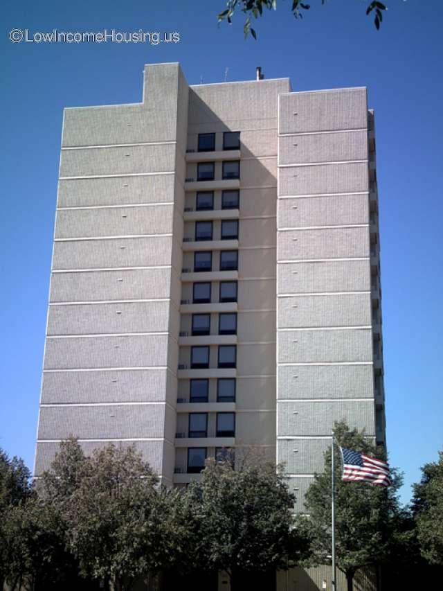 This is a concrete apartment block consisting of approximately 26  or more units serviced by an elevator.