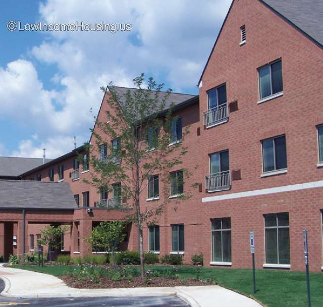 Bright red brick construction with covered entrance way give access to three twin story construction with floor to ceiling window units