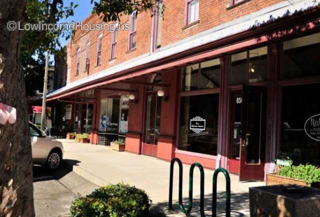 Red brick store front with variety of products available to purchase.  Ample sidewalk, Bicycle racks. Awning provides protection from the sun.