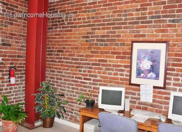 Interior view of spacious office with tasteful exposed bright red brick walls, steel columns frame work space.