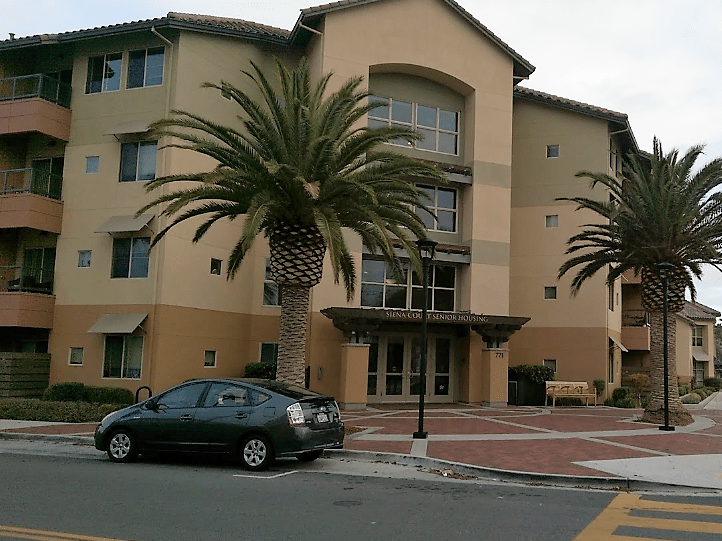 Corner streetview of four story building. Two large palm trees and light posts. a Toyota Prius is parked on the street. A bench is to the right of the entrance.